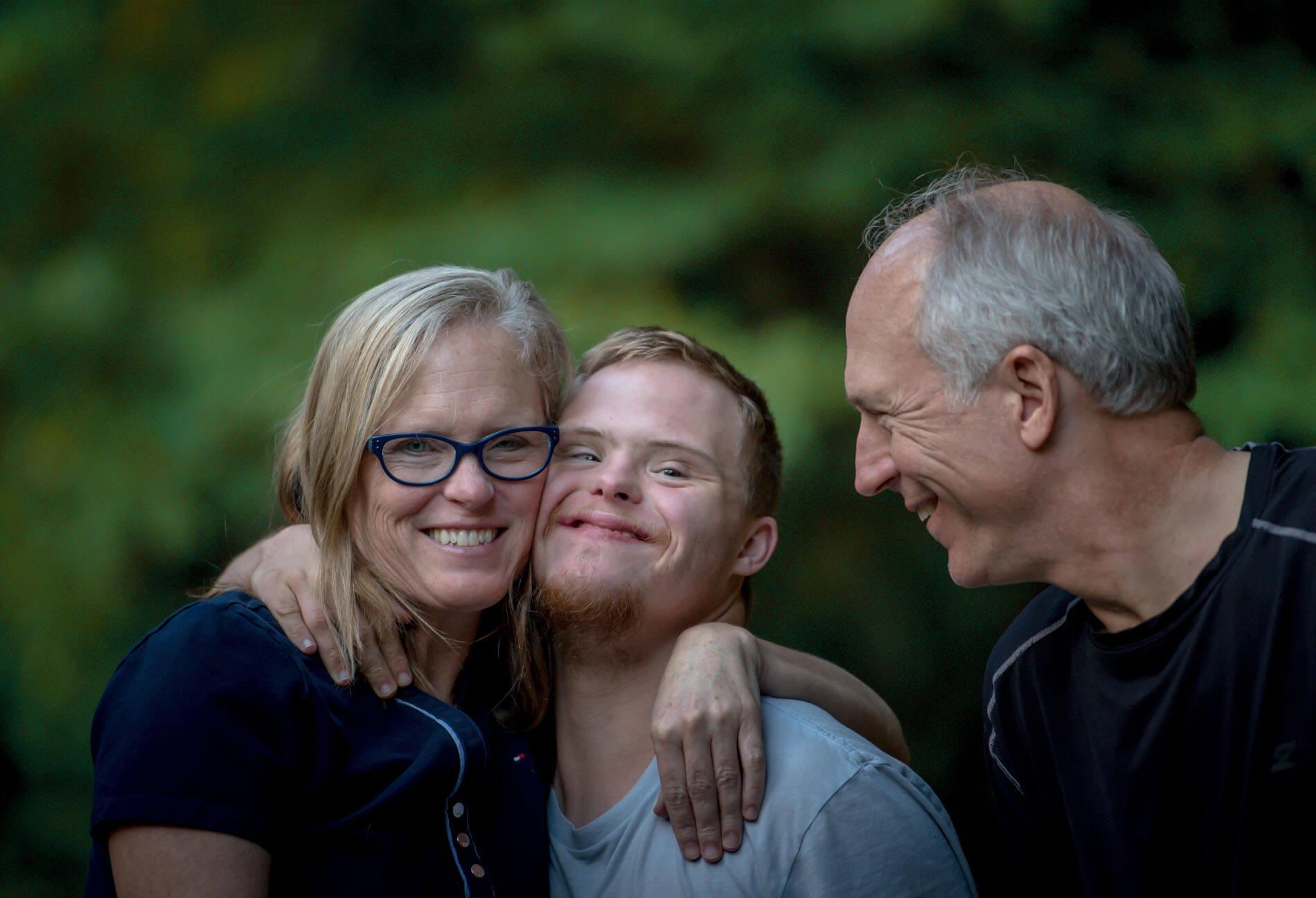Une famille heureuse. Une mère collant son fils handicapé et le père les regarde